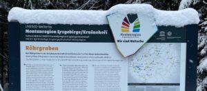 Infoschild der Montanregion Erzgebirge im Winter